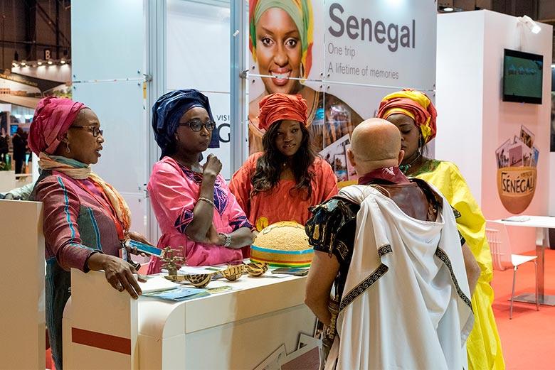 Un hombre disfrazado de romano habla con las chicas del Stand de Senegal en FITUR 2017 (Madrid)